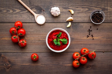 Ingredients for tomato sauce. Cherry tomatoes, garlic, green basil, black pepper, salt in spoon on dark wooden background top view
