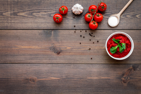 Ingredients for tomato sauce. Cherry tomatoes, garlic, green basil, black pepper, salt in spoon on dark wooden background top view copy space
