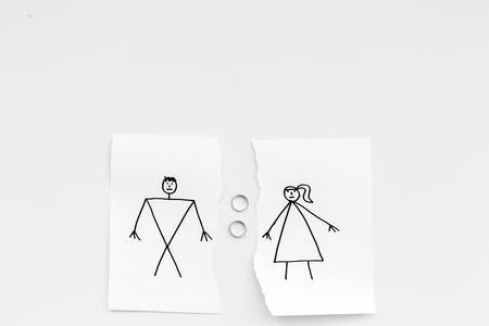 Concepto de divorcio o desmoronamiento. Hoja de papel rasgado con hombre y mujer dibujados, anillos de boda entre las partes sobre fondo blanco, espacio de copia de la vista superior Foto de archivo - 99935472