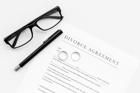 Divorce agreement. Wedding ring on document on white background top view copy space