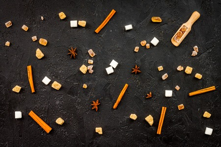 Seasoning for sweets and desserts background. Sugar, badian, cinnamon on black table top view Stock fotó
