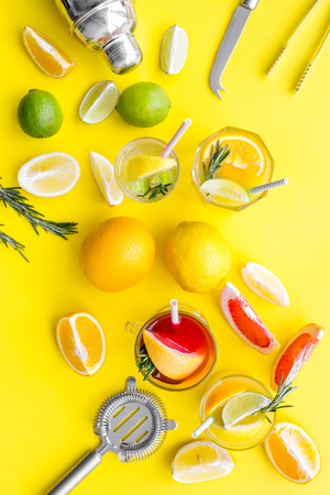 Bartender workplace for make fruit cocktail with alcohol. Shaker, strainer and other bar tools near citrus fruits and glass with cocktail on yellow background top view.
