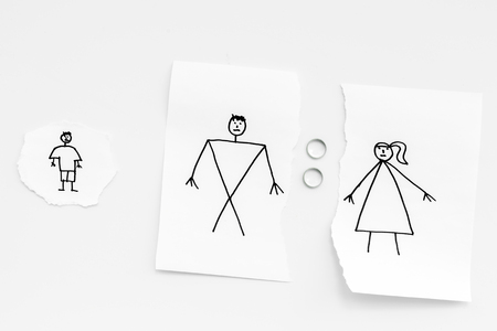 Child suffers from a divorce. Torn sheet of paper with drawn man, woman and child, wedding rings between parts on white background top view.