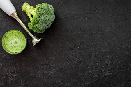 Cook green cream soup with vegetables. Broccoli and blender on black table top view.