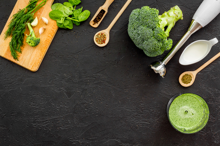Cook green cream soup with vegetables. Broccoli, cream, spices, blender on black table top view.