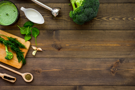Cook green cream soup with vegetables. Broccoli, cream, spices, blender on dark wooden table top view. Stock Photo