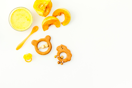 Healthy food for little baby. Puree with pumpkin near pacifier and toys on white background top view.