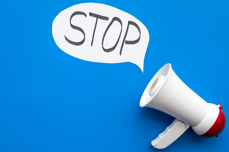 Demand to stop concept. Megaphone near cloud with word stop on blue background top view.