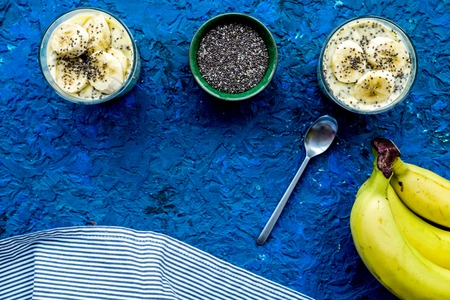 Homemade banana pudding with chia seeds on blue background with blue tablecloth top view. Stock Photo