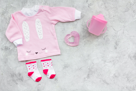 Newborn babys background. Clothes for small girl with booties on grey background top view copy space