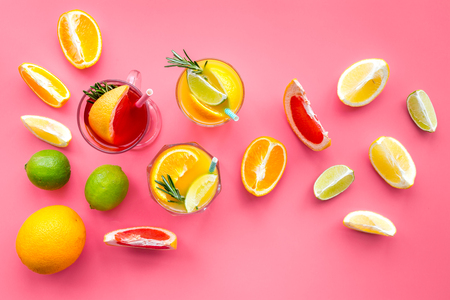 Tropical fruit cocktail with alcohol. Glass with beverage near oranges, grapefruit, lime and rosemary on pink background top view copy space Stock Photo