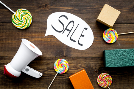 Sale concept with megaphone. Declare the sale. Electronic megaphone near word sale in cloud, gift boxes and sweets on dark wooden background top view