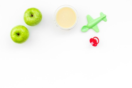 Fruit puree for baby. Jar with food near apple, pacifier, toys on white background top view. Stock Photo