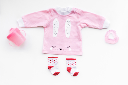 Newborn babys background. Clothes for small girl with booties on white top view.
