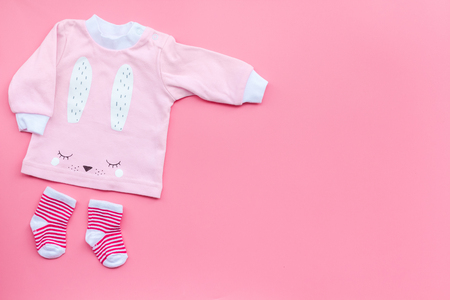 Newborn babys background. Clothes for small girl with booties on pink background top view.