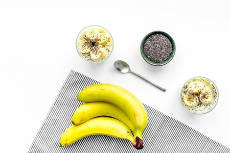 Light healthy snack. Banana pudding with chia seeds on white table with blue tablecloth top view. Stock Photo