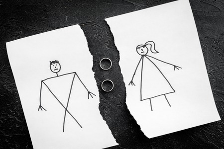Divorce or falling apart concept. Torn sheet of paper with drawn man and woman, wedding rings between parts on black background top view. Stock fotó