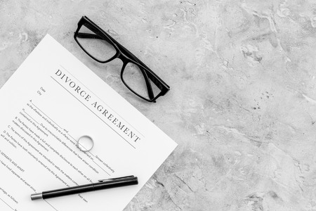 Divorce agreement. Wedding ring on document on grey background top view copy space