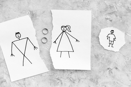 Child suffers from a divorce. Torn sheet of paper with drawn man, woman and child, wedding rings between parts on grey background top view