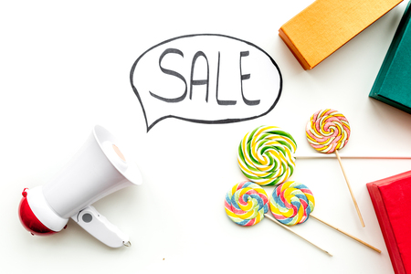 Sale concept with megaphone. Declare the sale. Electronic megaphone near word sale in cloud, gift boxes and sweets on white background top view copy space Фото со стока