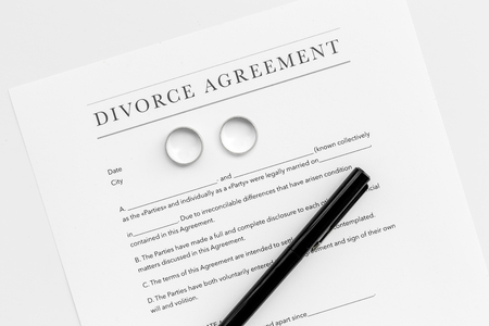 Divorce agreement. Wedding ring on document on white background top view Stock Photo