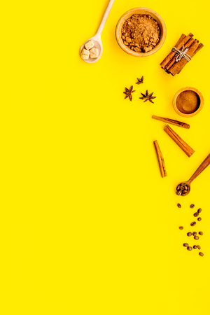 Ingredients for sweet bakery. Cinnamon, cocoa, sugar, badian on yellow table top view copy space Stock Photo