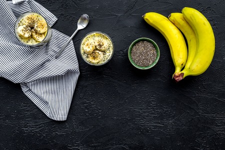 Banana pudding with chia seeds as low-calorie tasty appetizer. Black background with blue tablecloth top view space for text