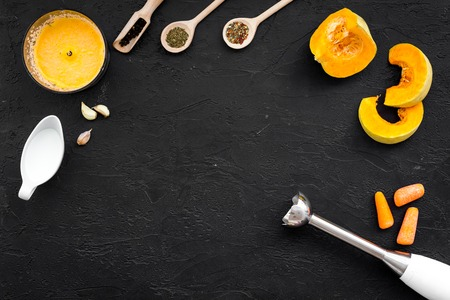 Cook orange cream soup with vegetables. Pumpkin, cream, spices, blender on black background top view copy space Stock Photo