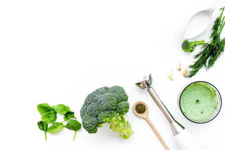Cook green cream soup with vegetables. Broccoli, cream, spices, blender on white table top view copy space Stock Photo