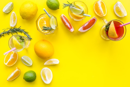 Concept of alcoholic cocktail with fruits. Glass with beverage near oranges, grapefruit, lime and rosemary on yellow background top view.
