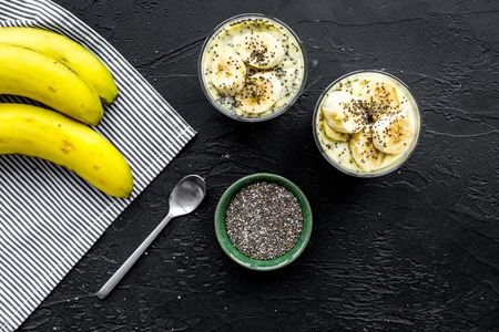 Banana pudding with chia seeds as low-calorie tasty appetizer. Black background with blue tablecloth top view. Standard-Bild