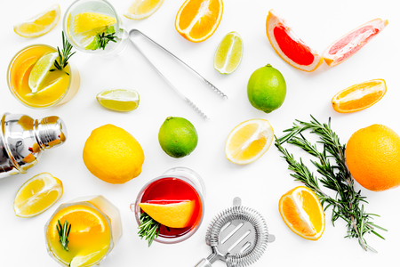 Bartender workplace for make fruit cocktail with alcohol. Shaker, strainer and other bar tools near citrus fruits and glass with cocktail on white background top view. Stock Photo