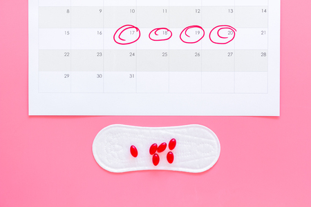 Menstruation cycle concept. Menstruation calendar with sanitary pads and contraceptive pills on pink background top view. Stock Photo