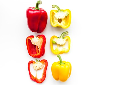 Layout of red and yellow sweet bell pepper slices on white background top view pattern copy space