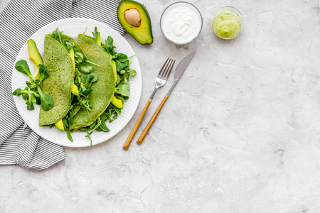 Spinach pancakes with spinach leaves and avocado slices on plate on grey background top view copy space