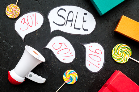 Sale concept with megaphone. Declare the sale. Electronic megaphone near word sale in cloud, gift boxes and sweets on black background top view Фото со стока