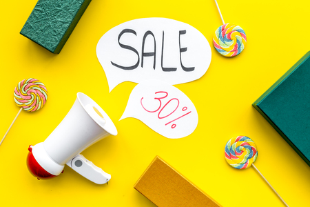 Sale concept with megaphone. Declare the sale. Electronic megaphone near word sale in cloud, gift boxes and sweets on yellow background top view