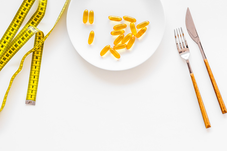 Dietary supplement for well-being. Fish oil or omega-3 capsules on plate near measuring tape on white background top view copy space Stock Photo