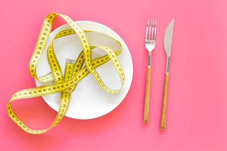 Diet for weight loss concept. Proper nutrition. Medical starvation. Empty plate with fork and knife near measuring tape on pink background top view