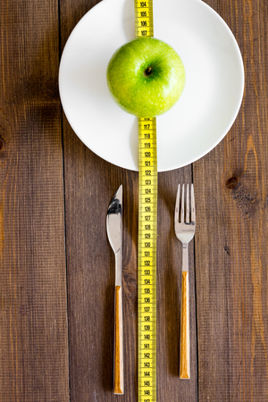 Proper nutrition with dietary fibre for weight loss. Apple on plate near measuring tape on dark wooden background top view