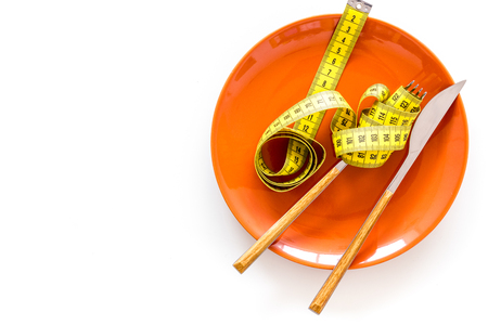 Diet for weight loss concept. Proper nutrition. Medical starvation. Empty plate with fork and knife near measuring tape on white background top view space for text