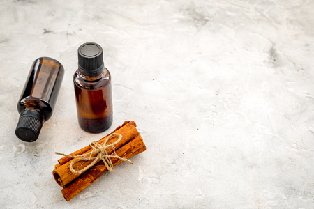 Cinnamon oil for cooking, aromatherapy, skin care. Bottles near cinnamon sticks on grey background space for text Standard-Bild