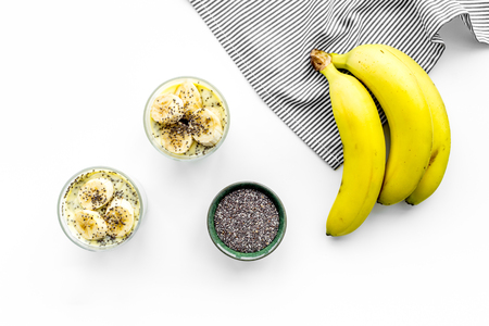 Light healthy snack. Banana pudding with chia seeds on white table with blue tablecloth top view
