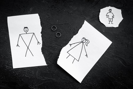 Child suffers from a divorce. Torn sheet of paper with drawn man, woman and child, wedding rings between parts on black background top view Stock fotó