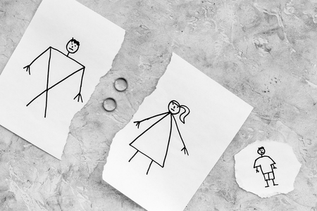 Child suffers from a divorce. Torn sheet of paper with drawn man, woman and child, wedding rings between parts on grey background top view copy space 版權商用圖片