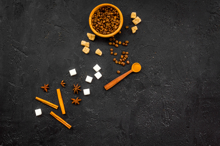 Ingredients for sweet bakery. Cinnamon, cocoa, sugar, coffee on black table top view copy space