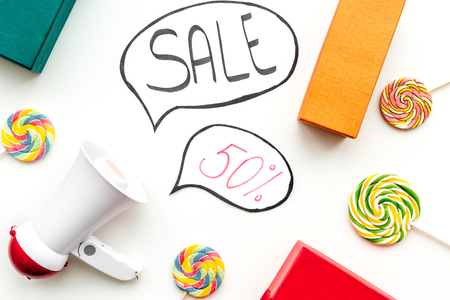 Sale concept with megaphone. Declare the sale. Electronic megaphone near word sale in cloud, gift boxes and sweets on white background top view