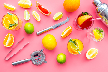 Bartender workplace for make fruit cocktail with alcohol. Shaker, strainer and other bar tools near citrus fruits and glass with cocktail on pink background top view pattern