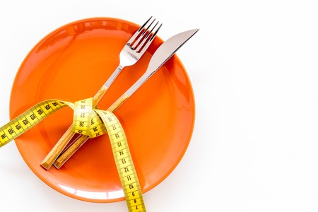 Diet for weight loss concept. Proper nutrition. Medical starvation. Empty plate with fork and knife near measuring tape on white background top view. Stock Photo