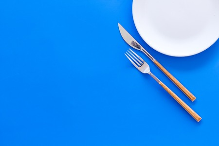 Proper nutrition for slimming. Empty plate with fork and knife on blue background top view. Stock Photo